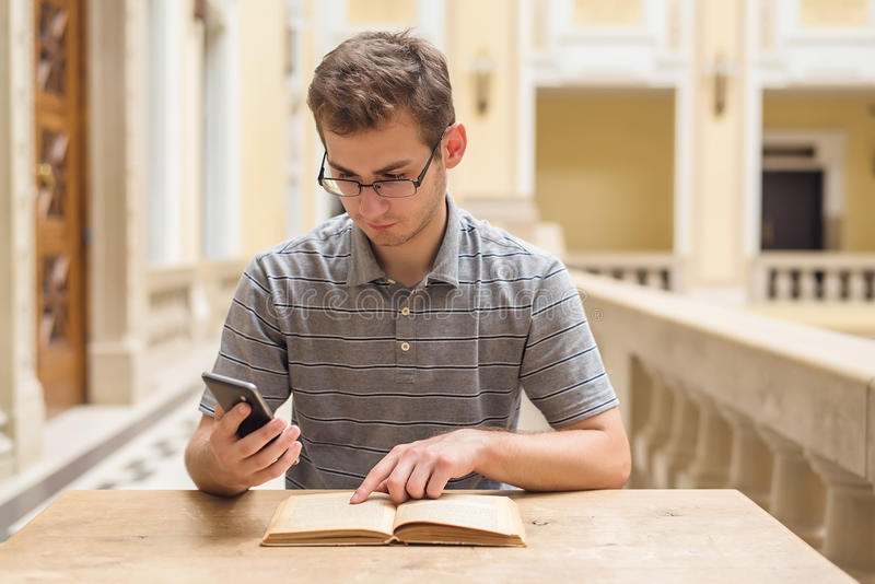 El individuo joven del estudiante que aprende y utiliza su teléfono imagen de archivo libre de regalías