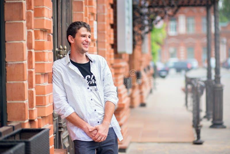 El individuo joven en costes de una camisa cerca de una pared de un ladrillo rojo del edificio y de las sonrisas fotos de archivo libres de regalías
