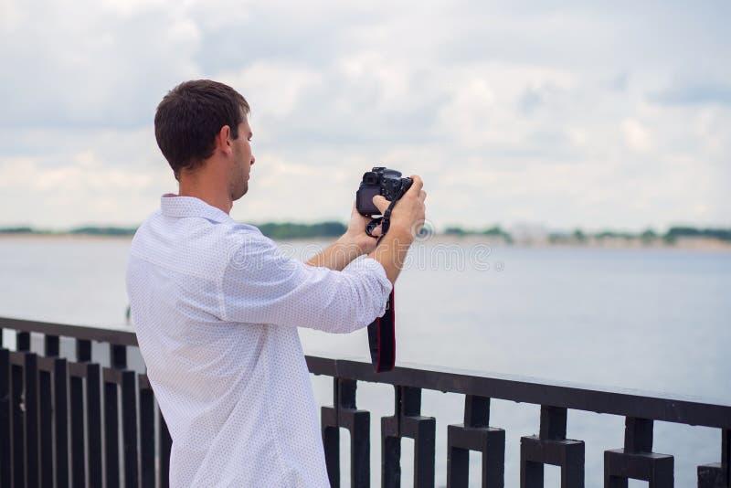 El individuo joven en una camisa blanca fotografía el río del terraplén en la cámara del espejo fotografía de archivo