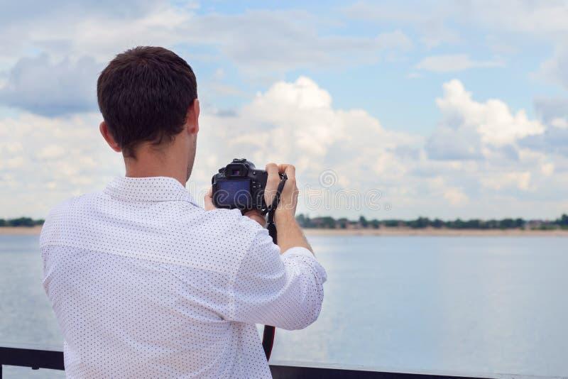 El individuo joven en una camisa blanca fotografía el río del terraplén en la cámara del espejo foto de archivo