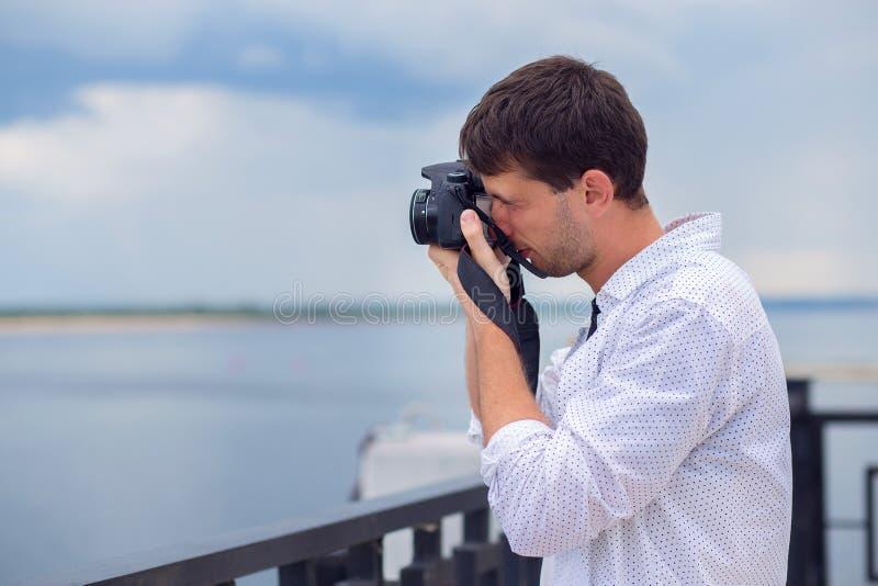 El individuo joven en una camisa blanca fotografía el río del terraplén en la cámara del espejo fotos de archivo libres de regalías