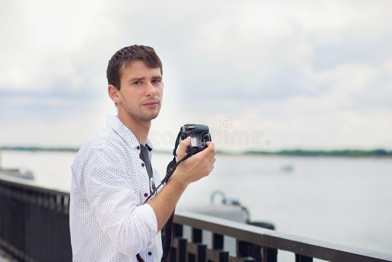 El individuo joven en una camisa blanca fotografía el río del terraplén en la cámara del espejo imagenes de archivo