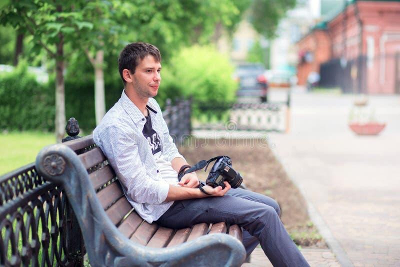 El individuo joven en una camisa blanca se sienta en una tienda en la calle en el parque, sostiene la cámara del espejo a disposi foto de archivo