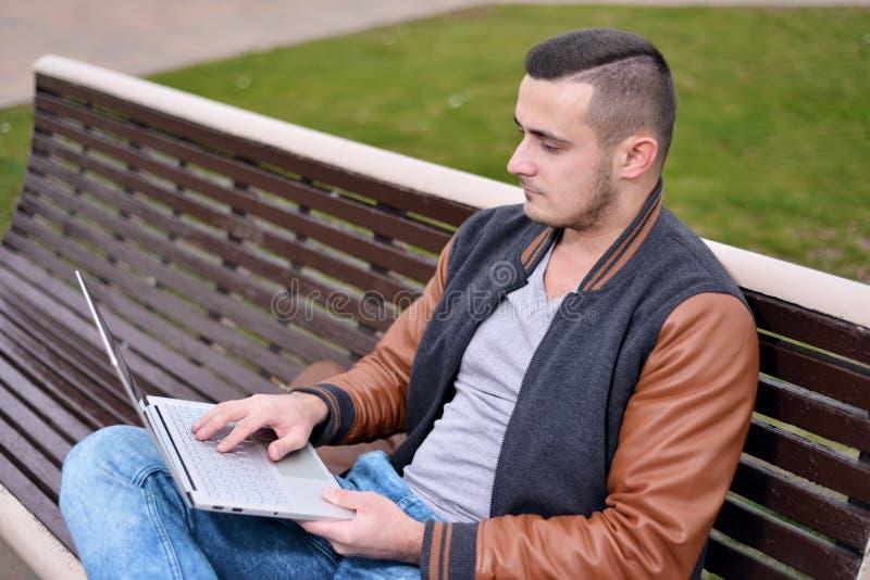 El individuo joven es freelancer que trabaja en el ordenador en la calle fotografía de archivo