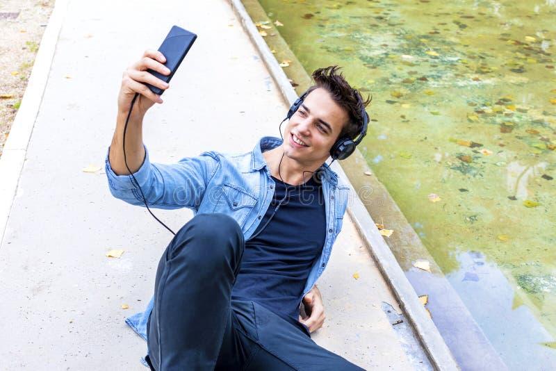 El individuo joven está haciendo el selfie en una cámara Él está llevando el tre casual fotografía de archivo libre de regalías