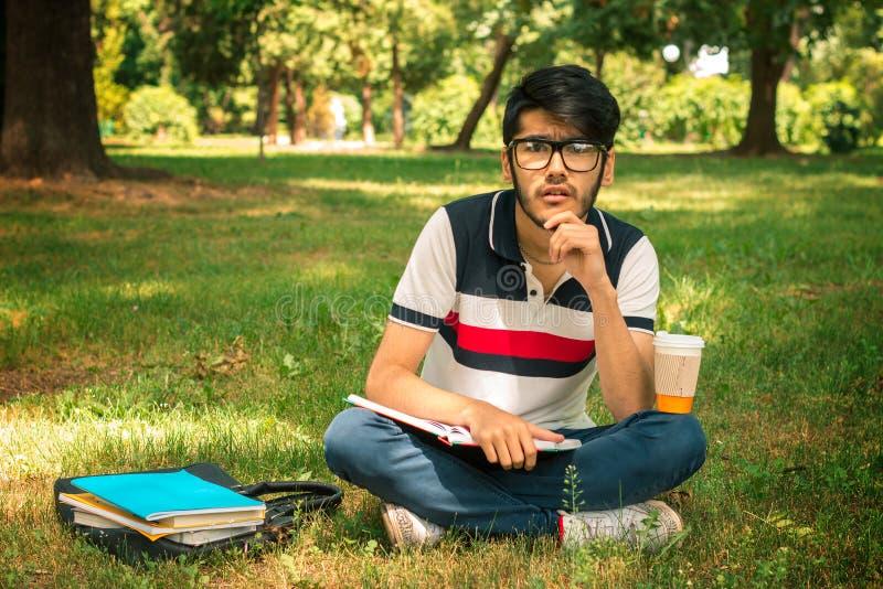 El individuo joven que se sienta en la hierba con los libros y anticipa en un día de verano foto de archivo