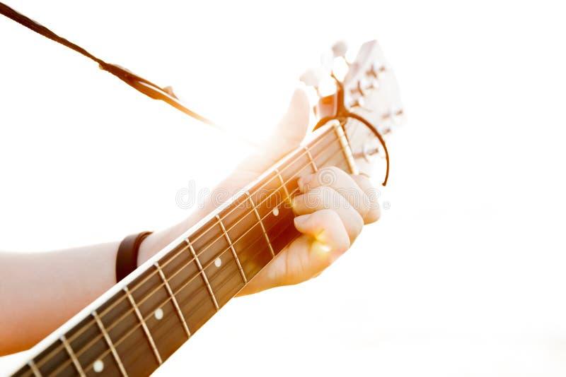 El individuo joven que toca la guitarra en alto-llave imagen de archivo