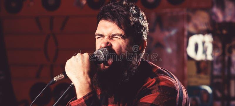 El individuo le gusta cantar de manera agresiva Músico con la canción del canto de la barba y del bigote en Karaoke Concepto de l fotografía de archivo libre de regalías