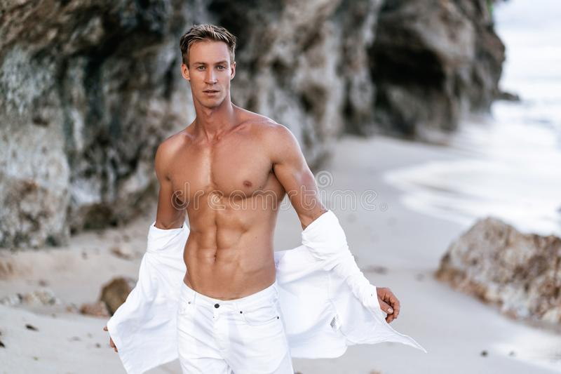 El individuo muscular atractivo con desnudo-de pecho en los pantalones blancos saca la camisa blanca en la playa, rocas en fondo imagen de archivo