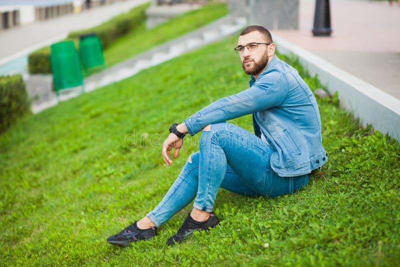 El individuo muscular fuerte joven se sienta en hierba y se relaja foto de archivo