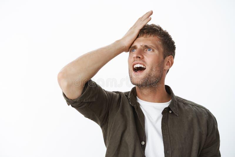 El individuo olvidadizo recuerda la frente de perforaci?n de la tarea importante con la palma que hace muecas con el pesar y el d foto de archivo