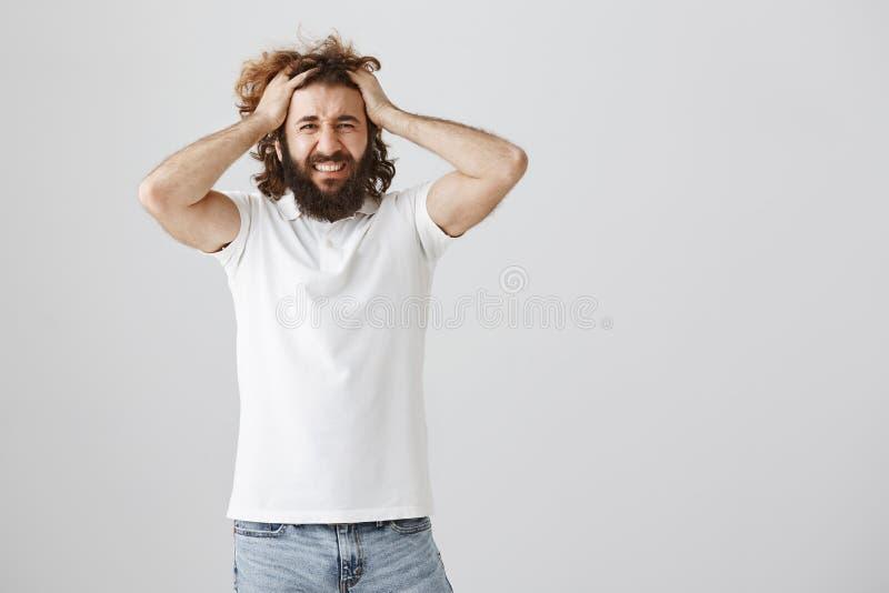 El individuo pierde genio de la mala suerte Retrato del hombre del este joven desgraciado y deprimido con la barba que tira del p foto de archivo