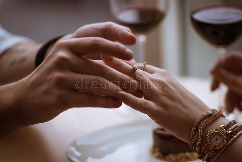 El individuo pone el anillo de la muchacha en su finger imagenes de archivo