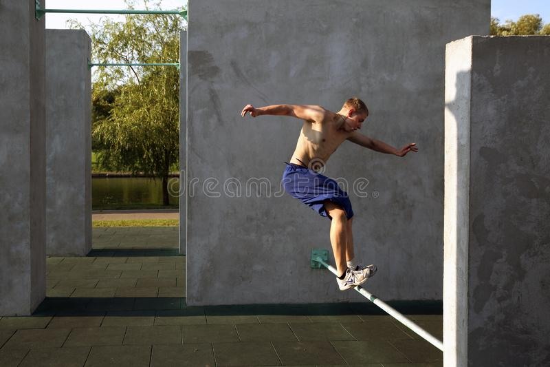 El individuo realiza un salto en el sitio para el parkour practicante fotos de archivo