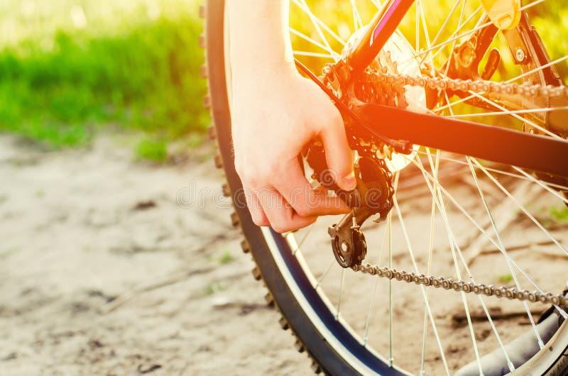 El individuo repara la bicicleta reparación de cadena unratitude en el camino, viaje, deportes, primer del ciclista fotos de archivo libres de regalías