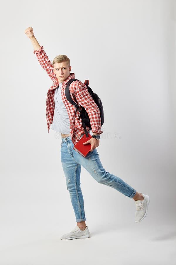 El individuo rubio divertido con la mochila negra en su hombro vestido en una camiseta blanca, la camisa a cuadros roja y los con fotografía de archivo