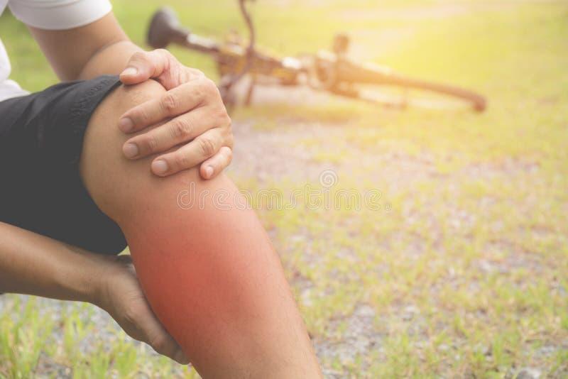 El individuo se aferra en una mala pierna El dolor en su pierna después del ejercicio foto de archivo