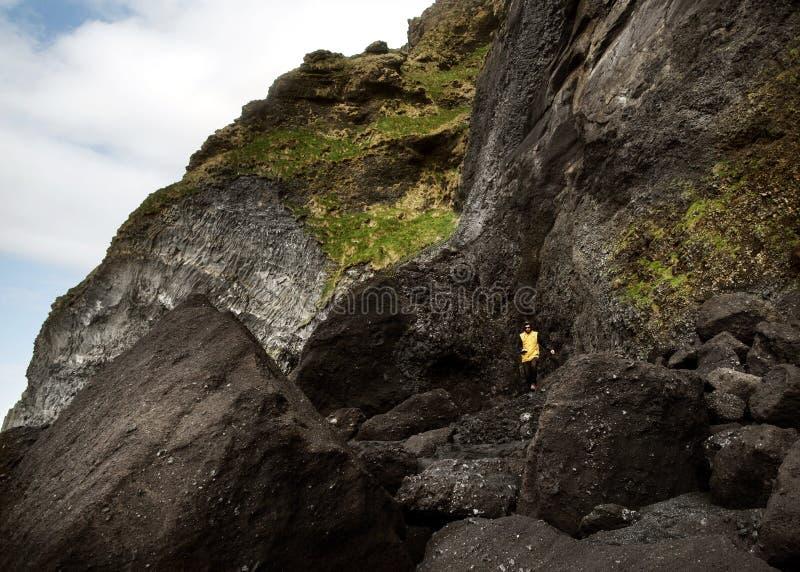 El individuo se coloca en una roca en una playa negra en Islandia, el concepto de fotografía de archivo libre de regalías