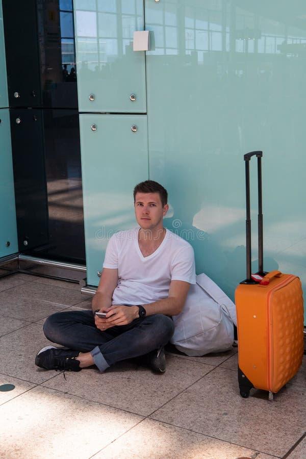 El individuo se está sentando en el piso en el aeropuerto Morenita en una camiseta blanca fotos de archivo libres de regalías