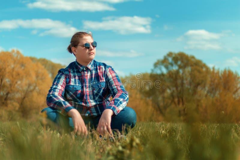 El individuo se sienta en la hierba en el campo contra los ?rboles imagenes de archivo