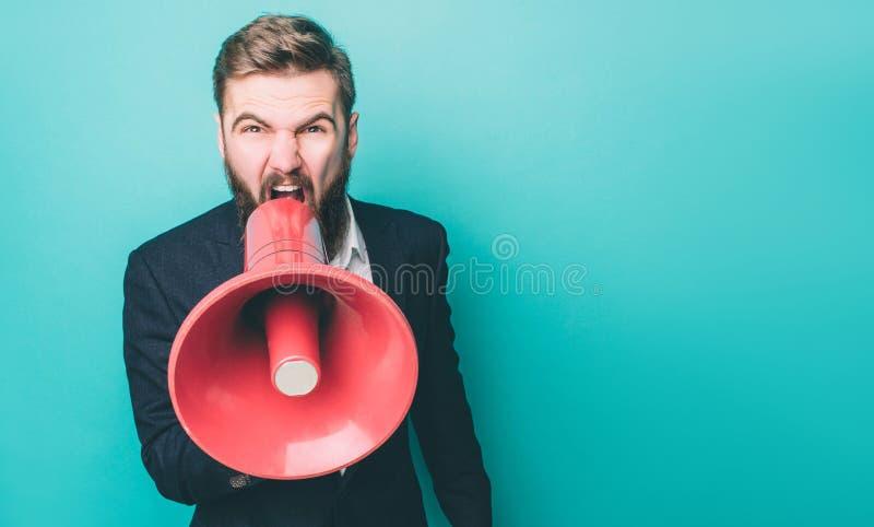 El individuo serio es de griterío y gritador usando el altavoz Él está haciendo eso mirando en la cámara directa imagenes de archivo
