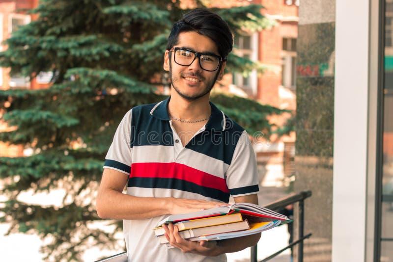 El individuo sonriente en vidrios mira en la cámara y guarda los libros fotos de archivo libres de regalías