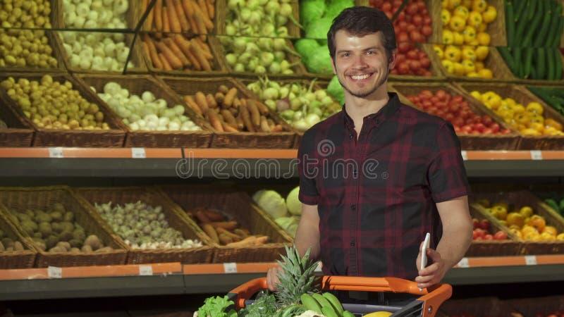 El individuo utiliza smartphone en el supermercado fotografía de archivo