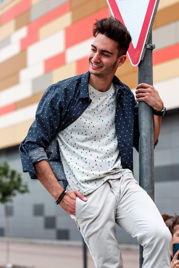 El individuo vestido en ropa del verano en estilo sport está engañando alrededor al lado de la señal de tráfico en el aparcamient imagen de archivo