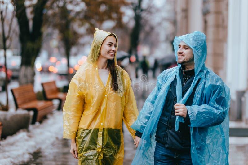 El individuo y la muchacha de amor en los impermeables amarillos y azules caminan en la calle bajo la lluvia fotografía de archivo libre de regalías