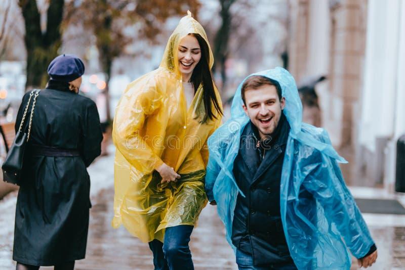 El individuo y la muchacha divertidos y cariñosos en impermeables amarillos y azules están corriendo bajo la lluvia afuera fotografía de archivo libre de regalías