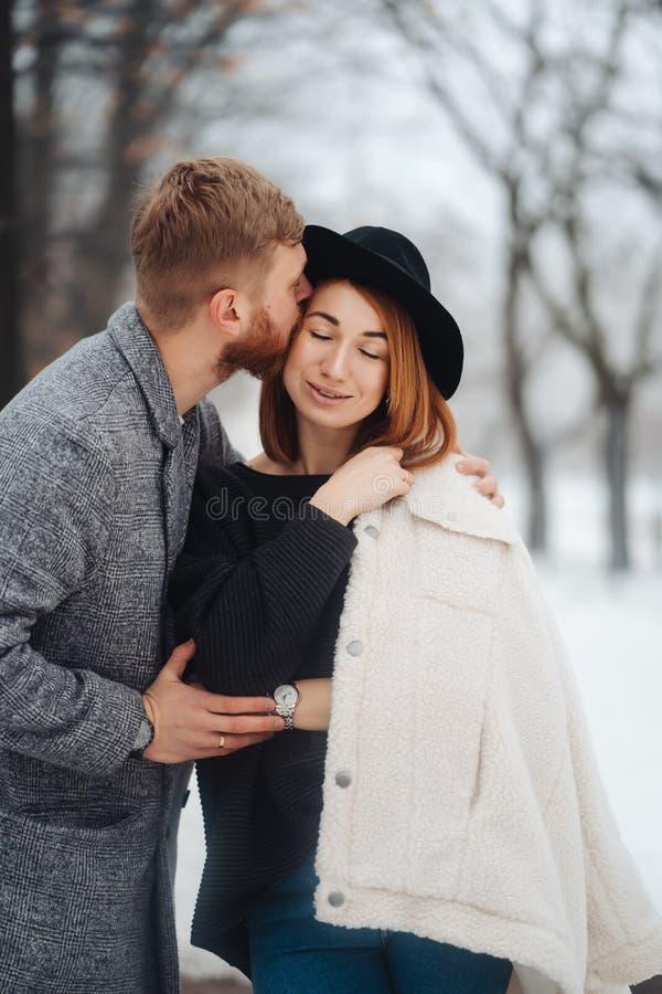 El individuo y la muchacha est?n descansando en el bosque del invierno foto de archivo libre de regalías