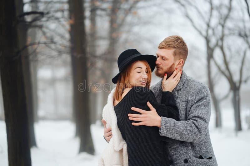 El individuo y la muchacha est?n descansando en el bosque del invierno imagen de archivo