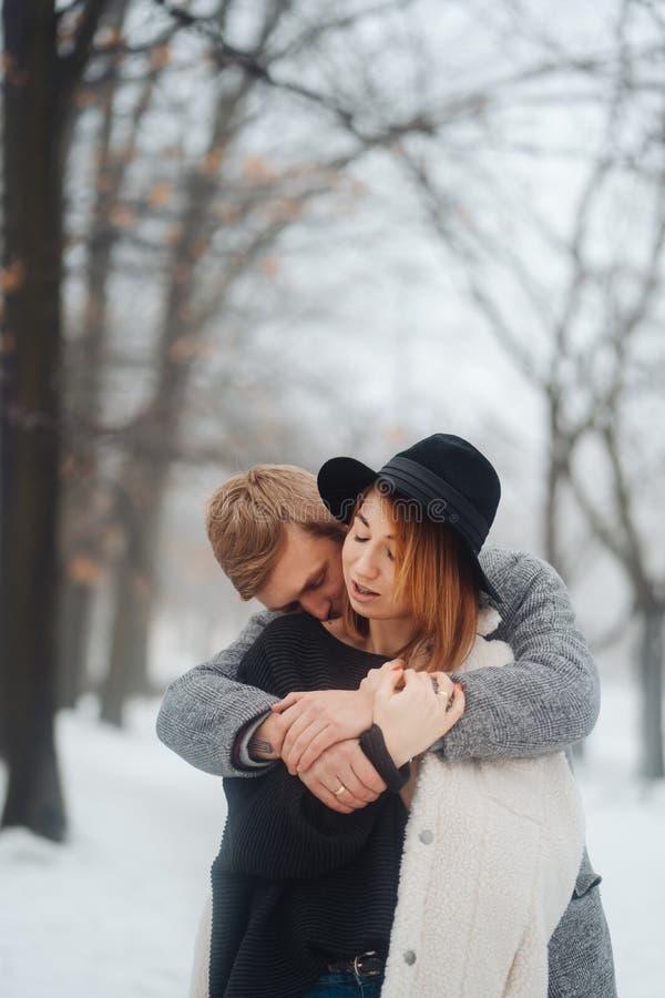 El individuo y la muchacha est?n descansando en el bosque del invierno foto de archivo