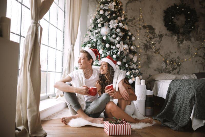 El individuo y la muchacha felices en las camisetas y los sombreros blancos de Santa Claus se sientan con las tazas rojas en el p fotografía de archivo