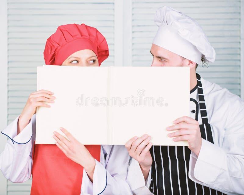 El individuo y la muchacha leyeron recetas del libro Concepto culinario La familia aprende receta Improve que cocina habilidad Re imágenes de archivo libres de regalías
