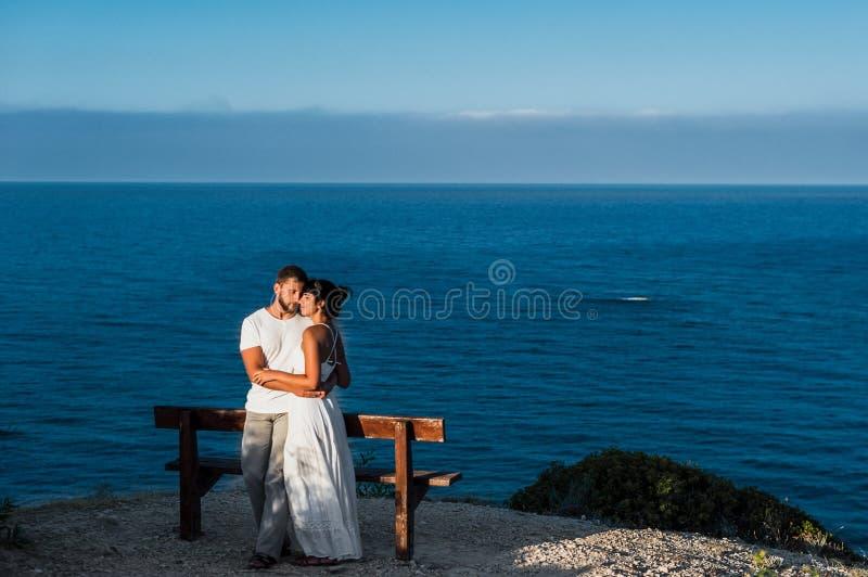 El individuo y la muchacha resuelve los primeros rayos del sol en el mar fotografía de archivo libre de regalías