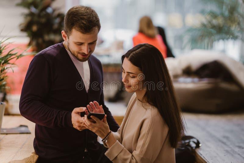 El individuo y la muchacha vestidos en suéteres y los vaqueros de amor se sientan en la tabla en el café y las miradas en el telé imágenes de archivo libres de regalías