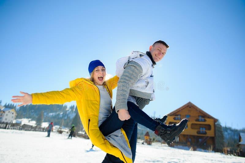 El individuo y una muchacha se están divirtiendo en el patio de una cabaña en una estación de esquí imagen de archivo
