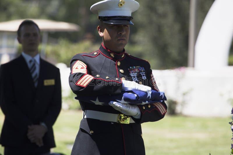 El infante de marina dobla la bandera en la ceremonia conmemorativa para el soldado caido de los E.E.U.U., PFC Zach Suarez, misió foto de archivo