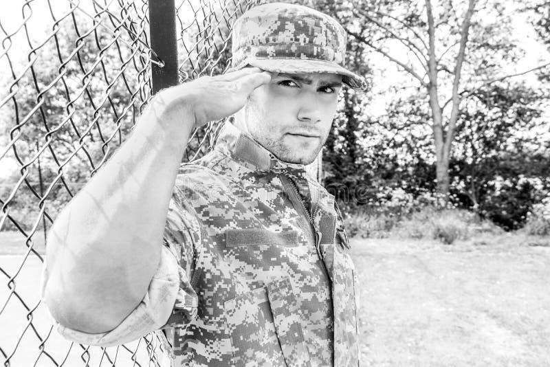 El infante de marina, soldado en su ejército cansa soportes a la atención y saluda en la base militar fotografía de archivo libre de regalías