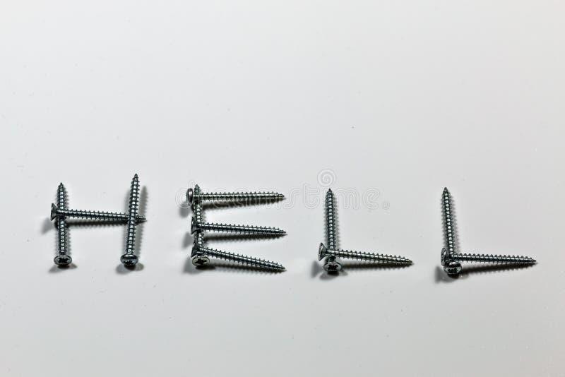 El infierno de la palabra escrito con los tornillos en un fondo blanco con reflexiones fotografía de archivo libre de regalías