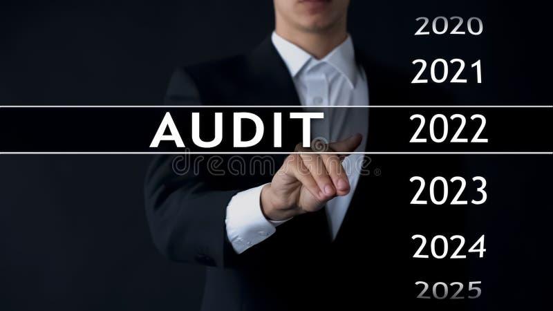 El informe de auditoría 2022, hombre de negocios encuentra datos en el estado financiero del archivo virtual foto de archivo