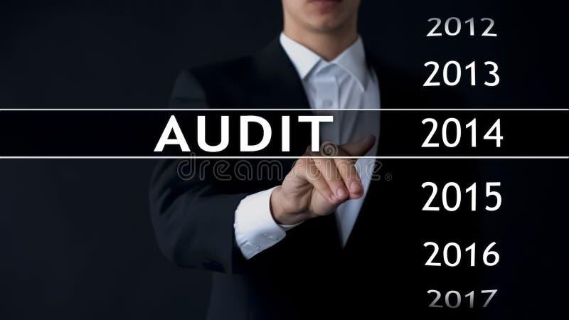 El informe de auditoría 2014, hombre de negocios encuentra datos en el estado financiero del archivo virtual imagen de archivo