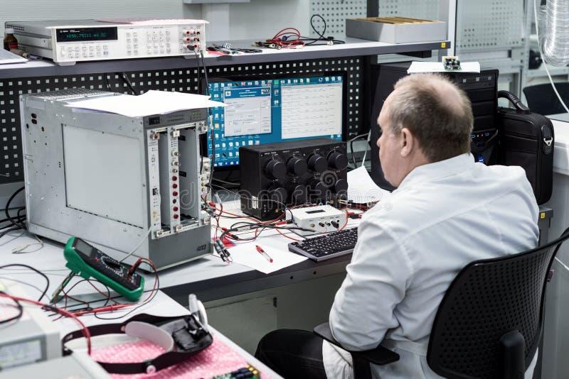 El ingeniero conduce una prueba de los módulos electrónicos acabados Laboratorio para probar y el ajuste de electrónico fotos de archivo