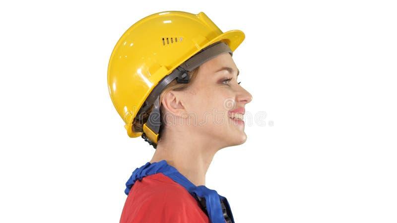 El ingeniero de la mujer joven con el casco de seguridad amarillo que camina y que sonríe en el fondo blanco fotos de archivo libres de regalías