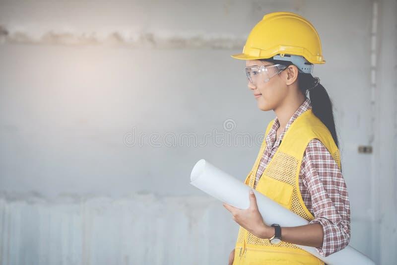 El ingeniero de sexo femenino del casco amarillo sostiene un modelo mientras que examina imagenes de archivo