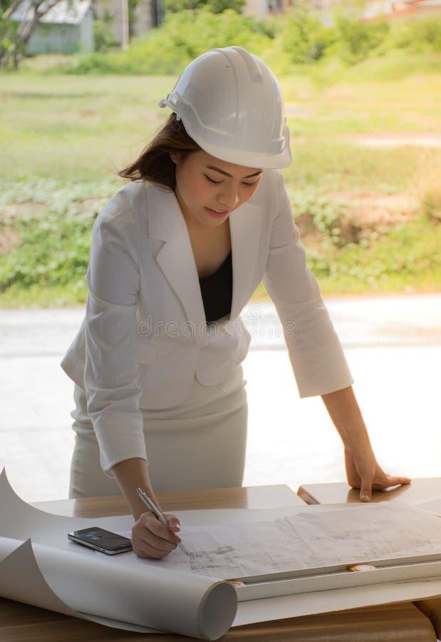 El ingeniero de sexo femenino del emplazamiento de la obra/los ingenieros jovenes está comprobando el plan fotos de archivo