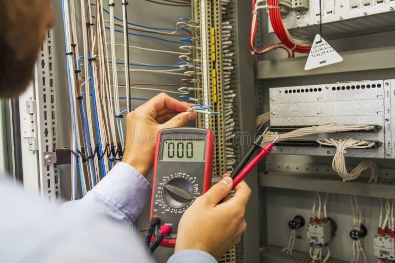 El ingeniero del electricista con el multímetro prueba el panel de control eléctrico del equipo de la automatización Especialista fotos de archivo