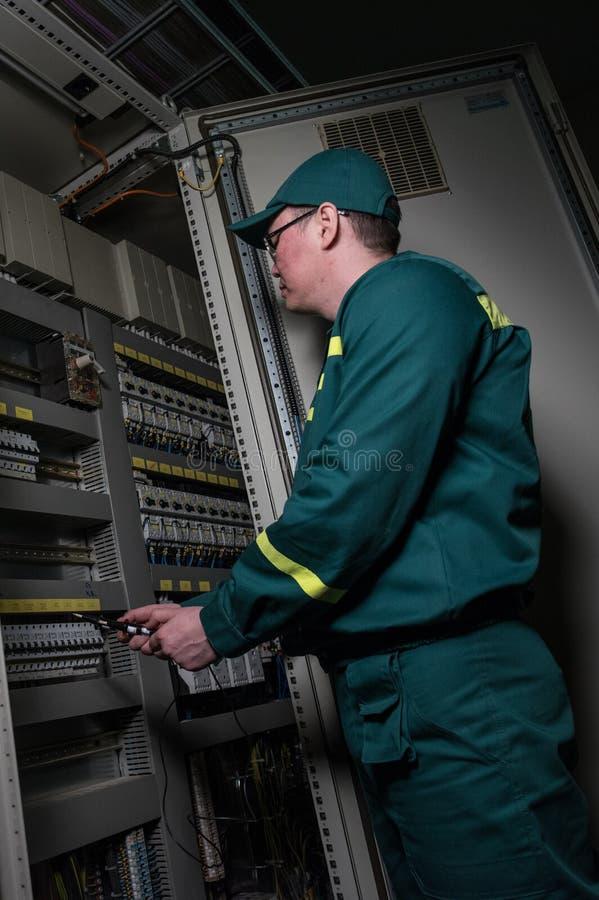 El ingeniero del electricista está probando el equipo eléctrico en una planta grande foto de archivo