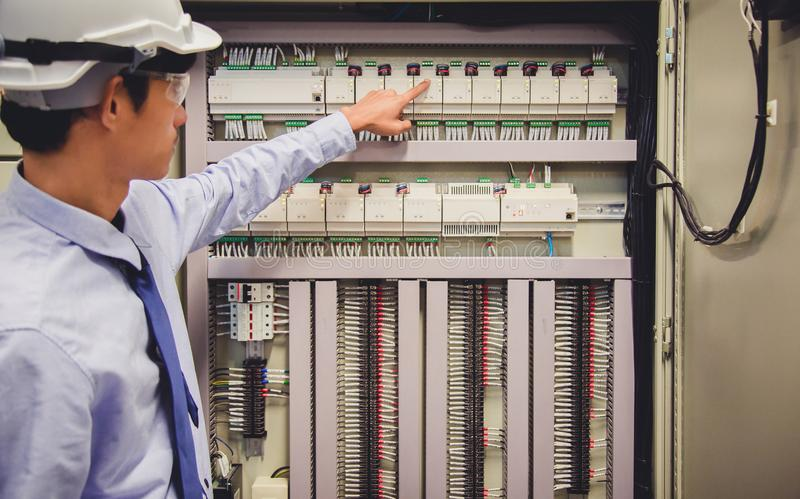 El ingeniero del electricista prueba el panel de control eléctrico de la central eléctrica de las instalaciones fotos de archivo